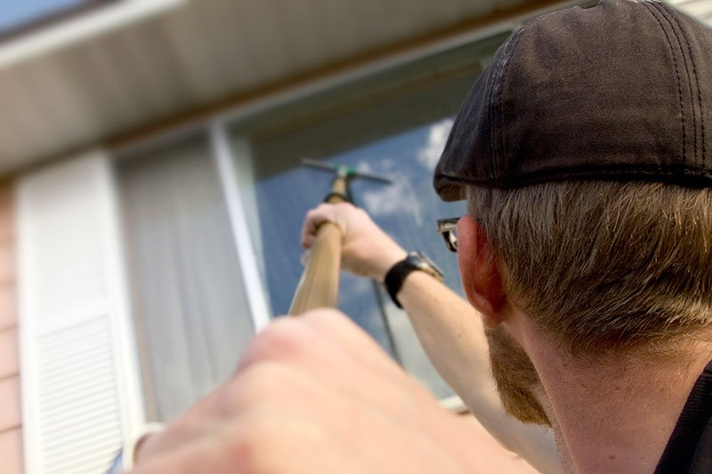 Cleaning window with pole mounted squeegee