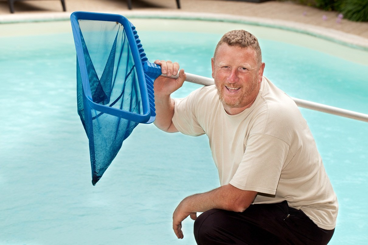A pool maintenance professional holding a pool rake and posing next to a residential pool he's cleaning