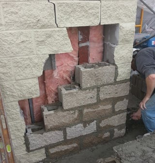 Block Laborer Repairing Damaged Wall