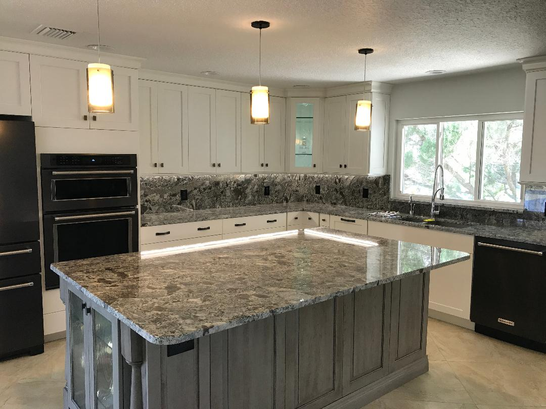 Ageless kitchen with huge custom Island featuring three drop down pendant lights.