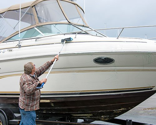 Caucasian Man Cleaning Power Boat With Long Brush