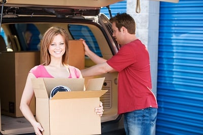 Couple unloading van at storage unit