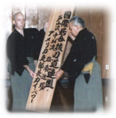 September 1994. Power sensei receives the International Battodo Federation's kanban from Sato Shimeo sensei (hanshi, 9th dan) in Tsurumi ward, Yokohama City, Japan. The kanban states from right to left: International Battodo Federation, Toyama Ryu, Nakamura Ryu Teaching Dojo, America Director, Guy Power.