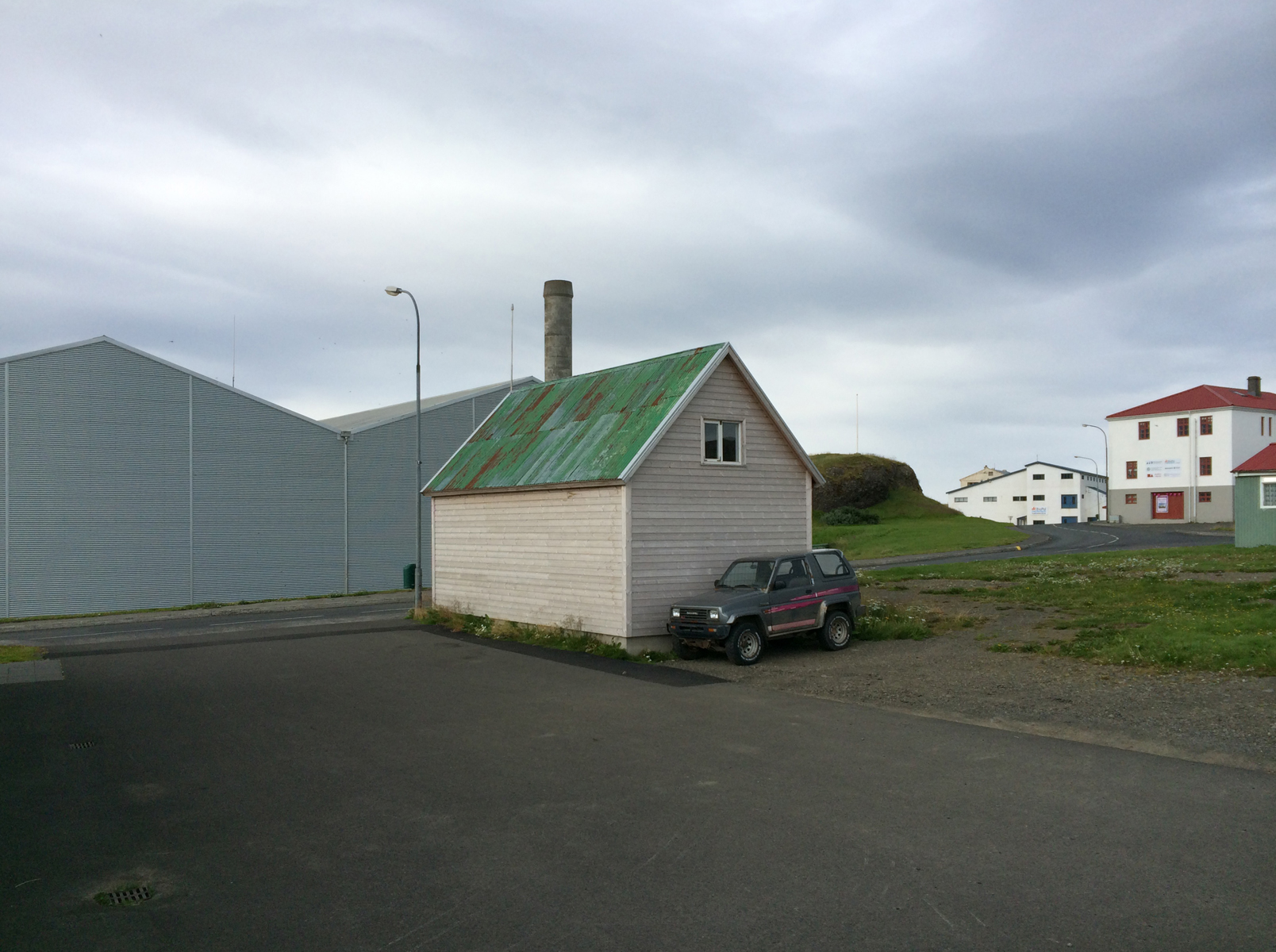 In expanse of asphalt and grey sky, a small building with a green metal roof.