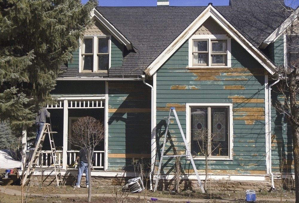 A home is scraped to prepare it for fresh paint.