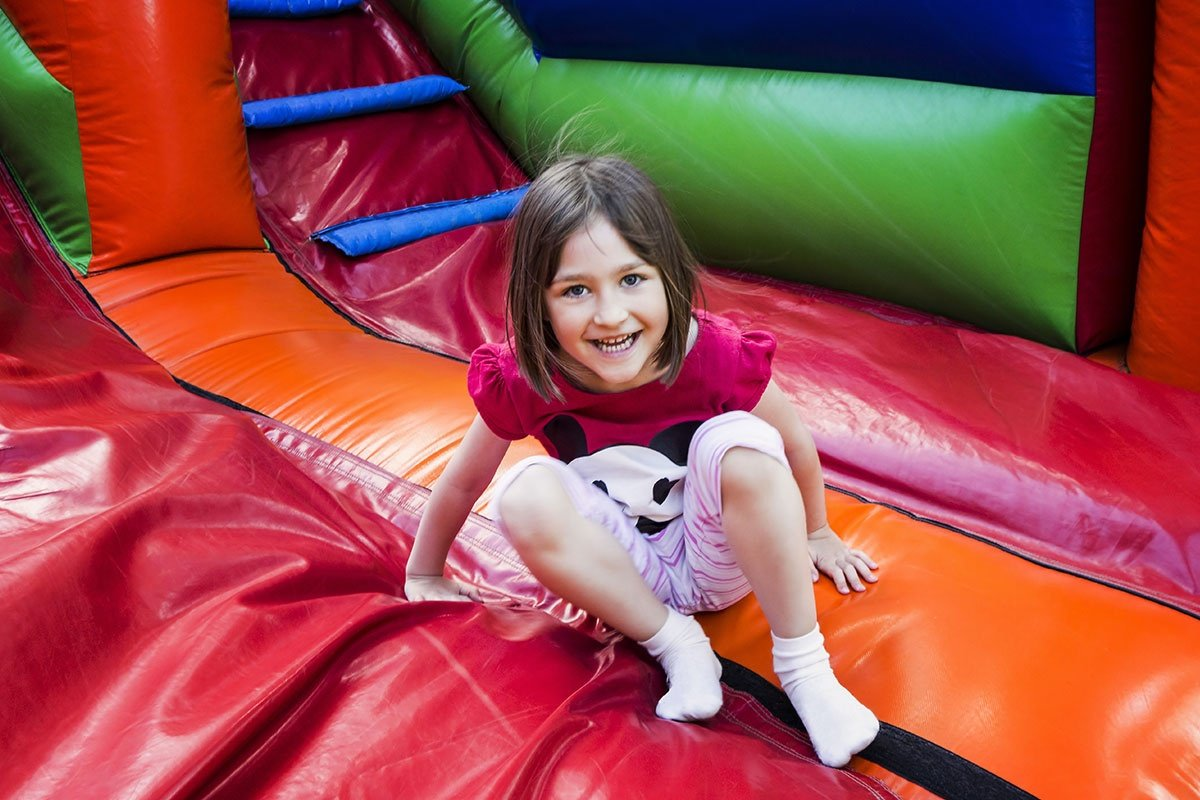 Girl Having Lots Of Fun On A Jumping Castle While Sliding