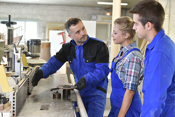 Professional Teacher Showing Carpentry Machinery