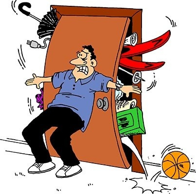 man holding items in a bulging closet in front of door