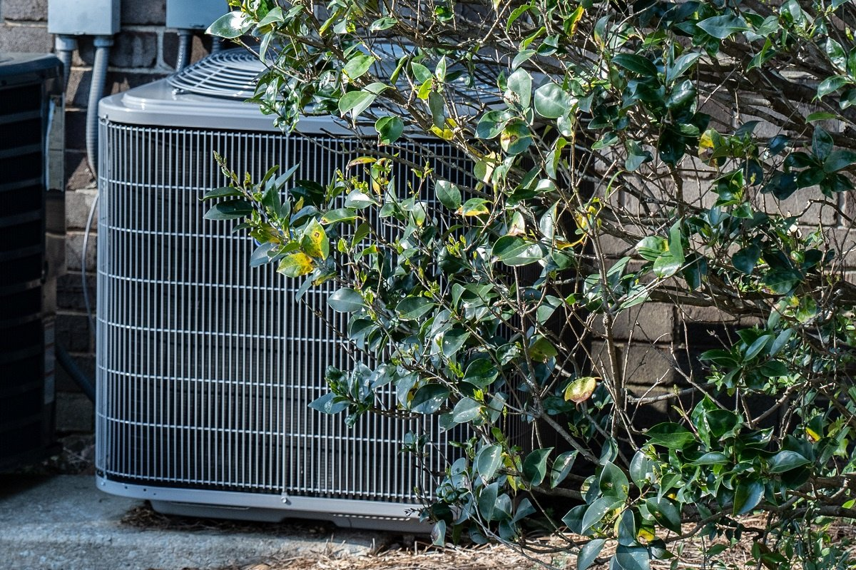 Residential HVAC unit by bush