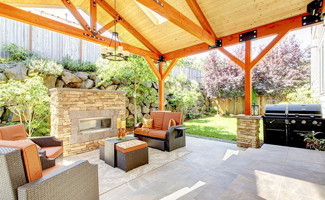 Exterior Covered Patio With Fireplace and Furniture