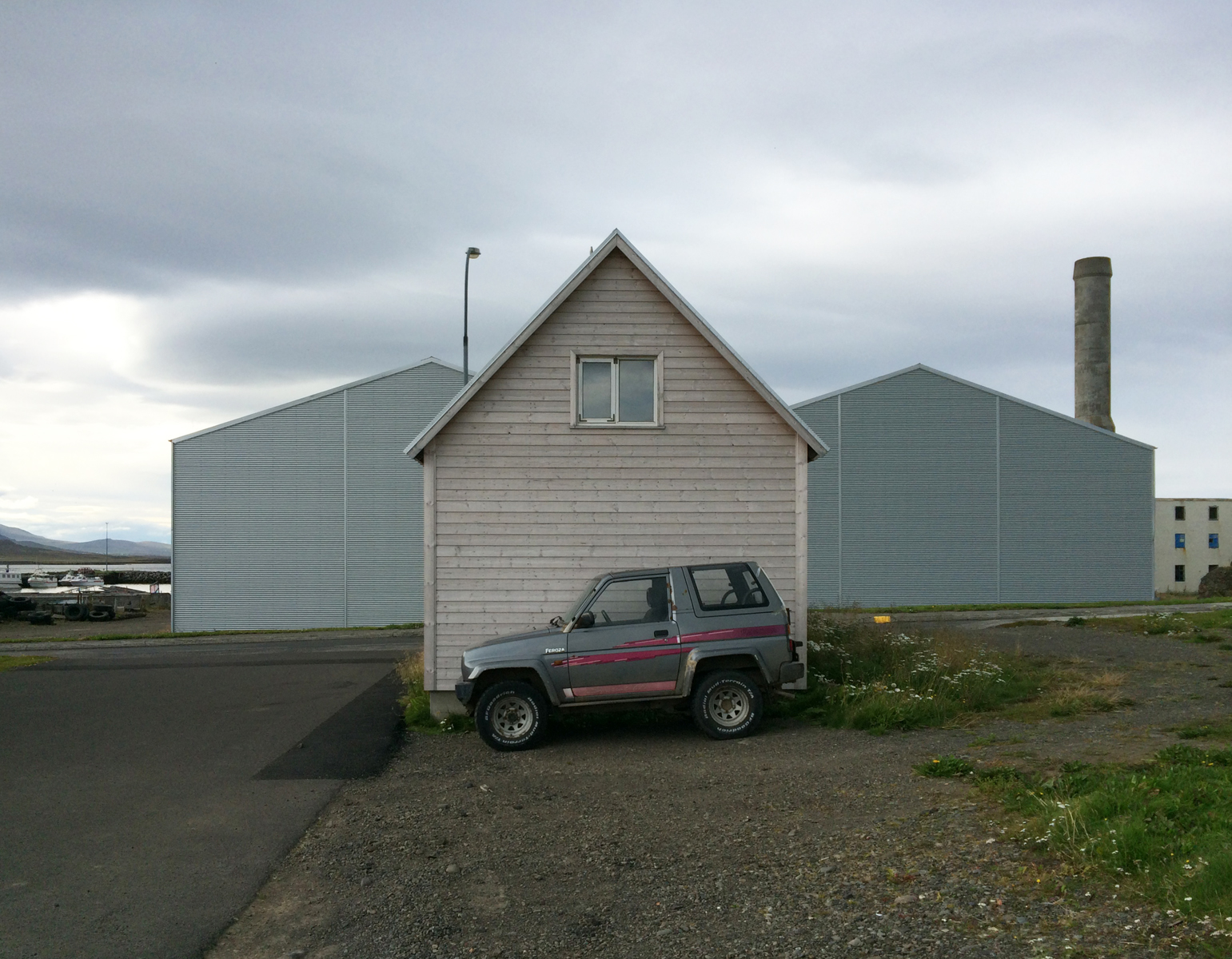 A small grey SUV parked in front of the peaked gable end of a small building.