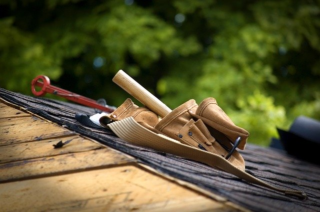 Roofer's Tool Belt with Wooden Hammer Hand Sticking Out On Roof