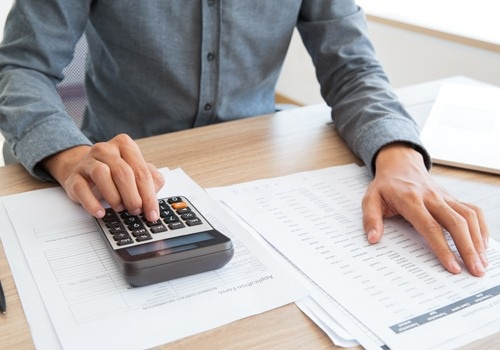 Accountant Calculating Income and Examining Report