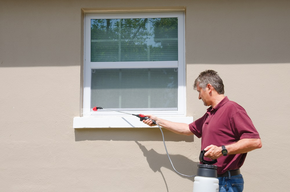 Man applying pesticide to window exterior