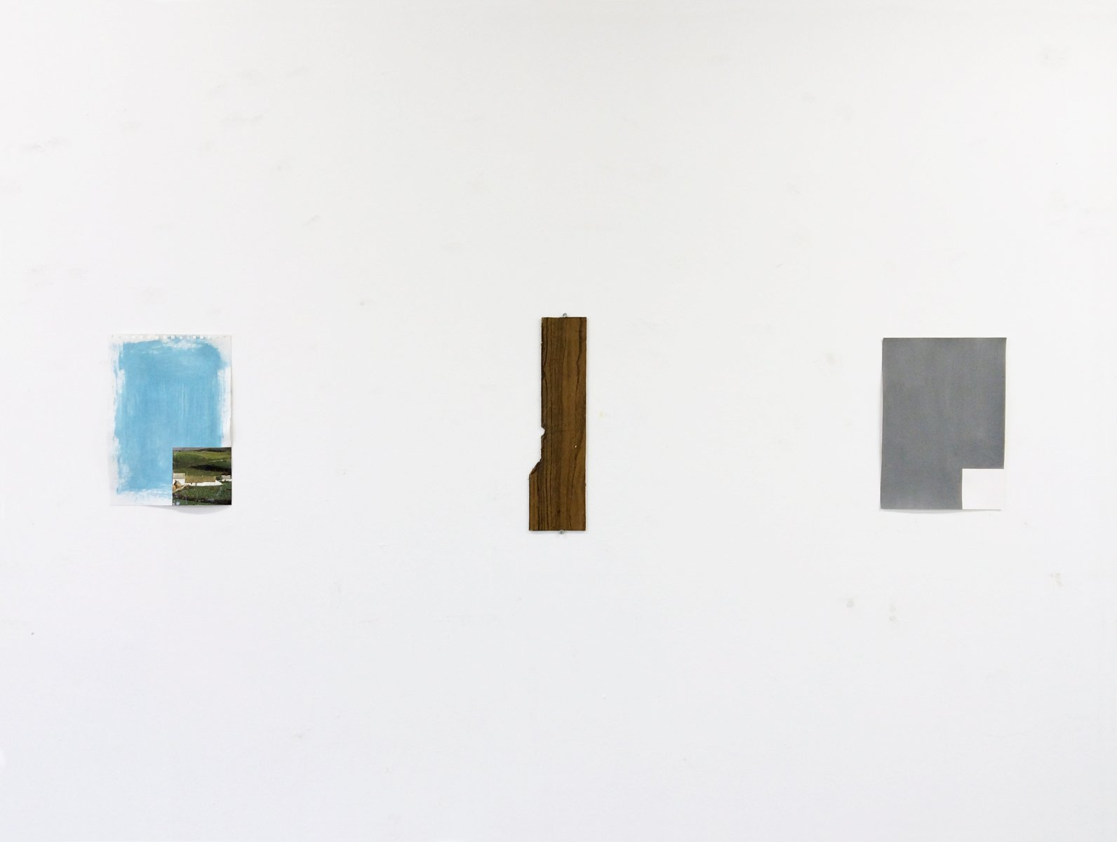 A minimalist collage, piece of wood panel and grey geometric drawing on a wall.