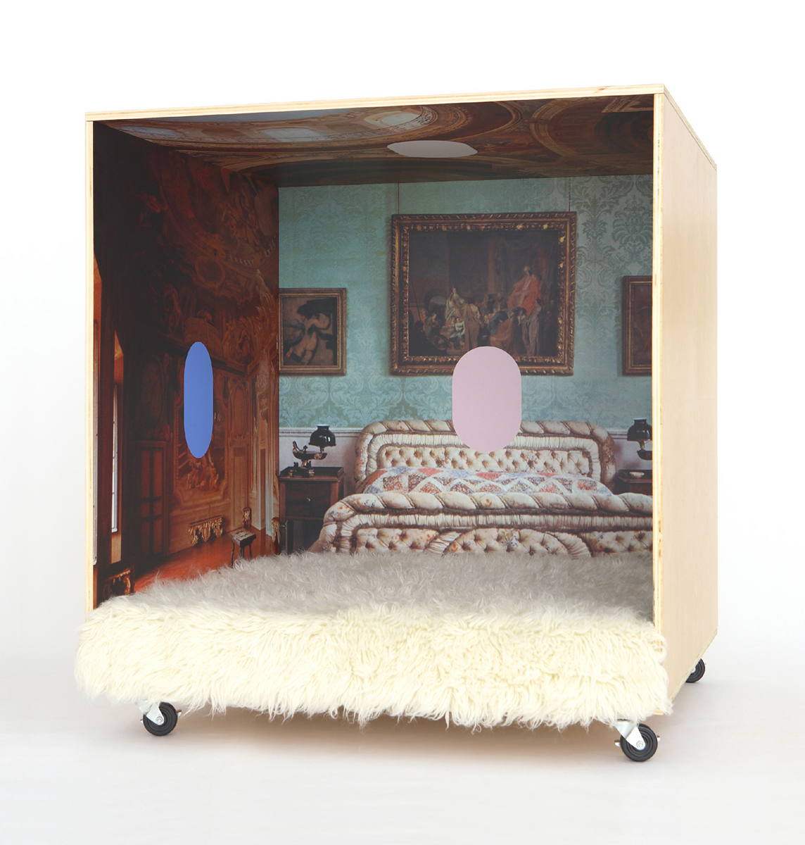 A plywood cube on wheels with an opulent interior with colorful oval graphics.