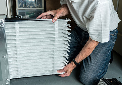Man Checking a Clean Folded Air Filter in the Hvac Furnace System
