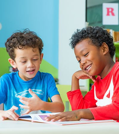 Two Boy Sit On Table And Reading Tale Book