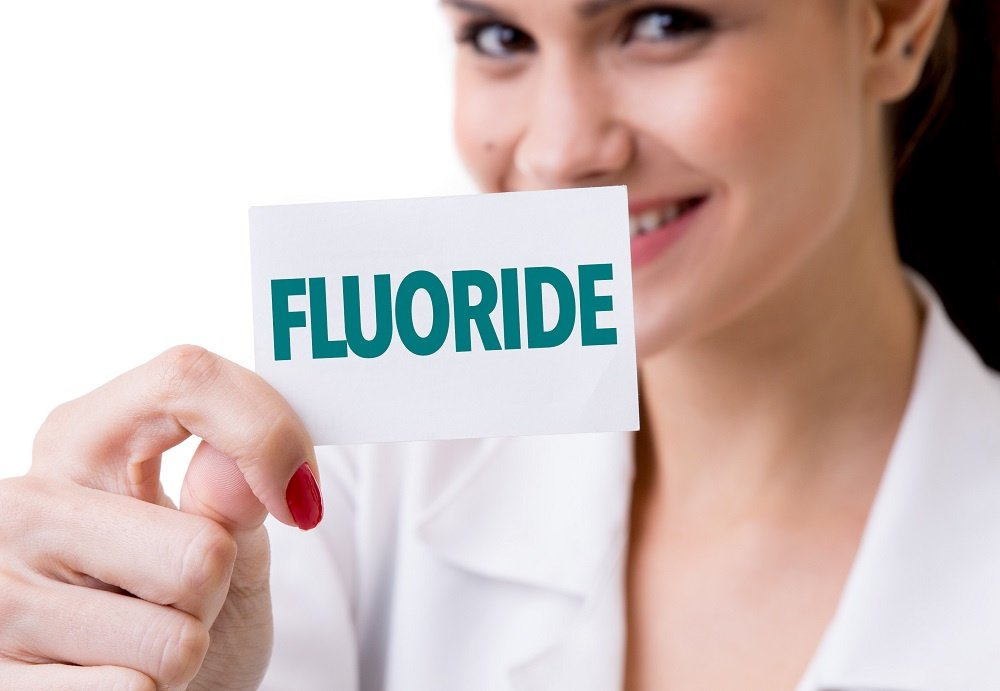 Woman holding up paper that says Fluoride