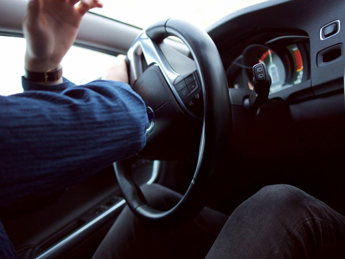 Man with hand on steering wheel driving a car