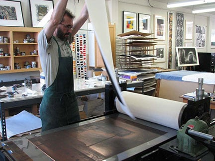 Printer David Avery pulling a print of Jenny Robinson's Third Street Factory