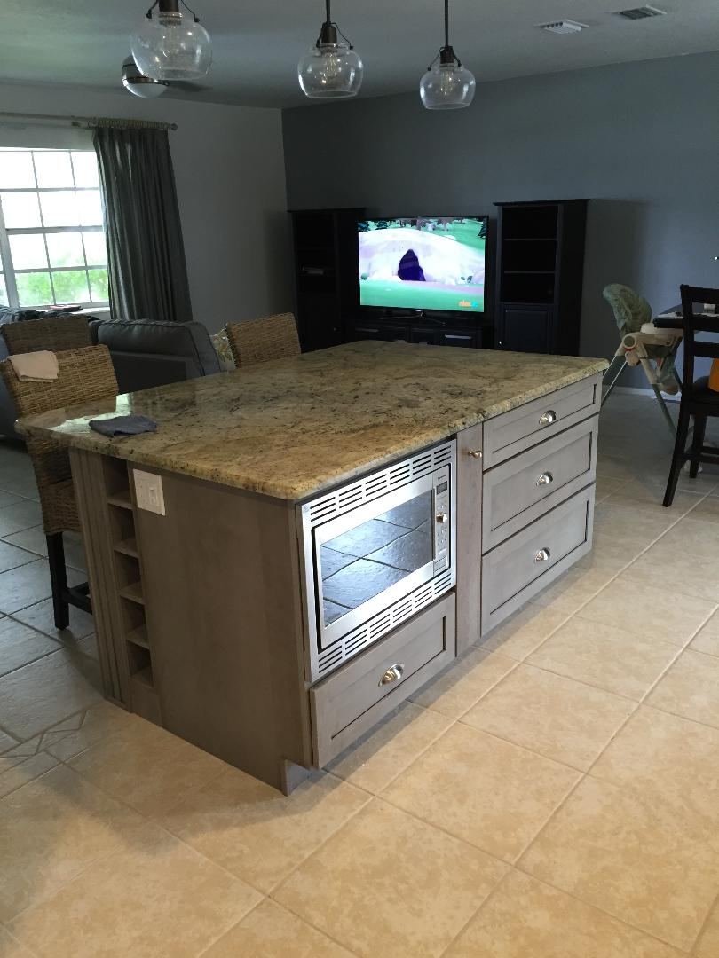Custom Island featuring an undermounted microwave oven with additional storage.