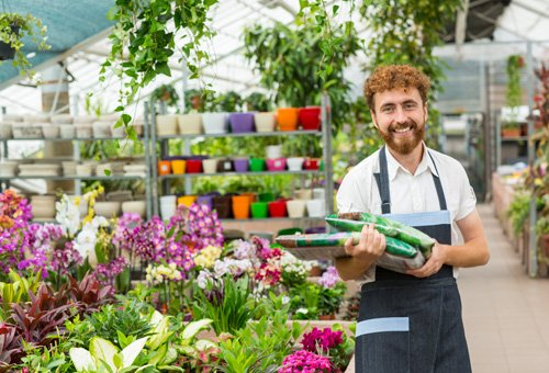 Gardener Holding Fertilizer Packs