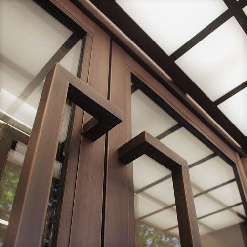 Bronze metal finish onto entrance doors. Artistic Metals.