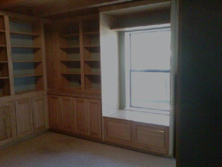 These office cabinets feature raised paneled doors,  window seat with storage underneath, cubby hole  above window, adjustable shelves and desk. Colonial  Maple hand wiped stain with clear coating finishes red oak wood.