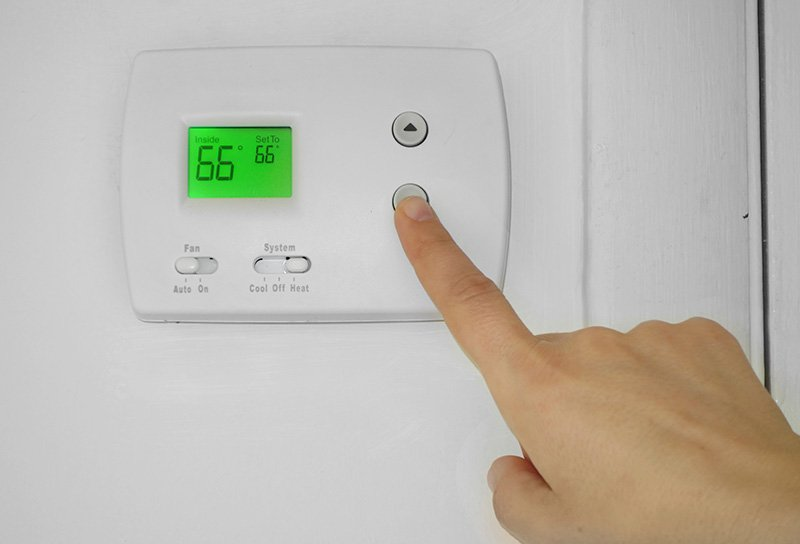 Person adjusting a wall thermostat temperature