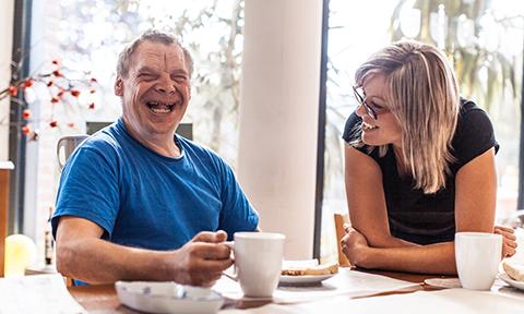 Man Laughing at Table