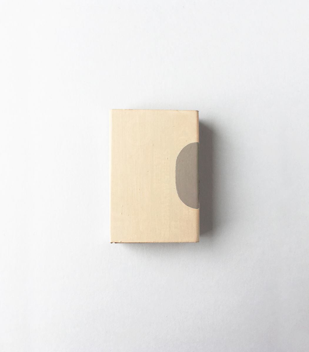 A matchbox with a bisected oval painted on one edge in taupe on cream.