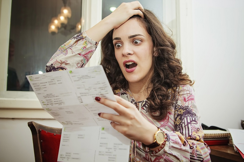 Woman Looking at Utility Bill and Shocked