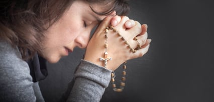 Woman Praying with Rosary