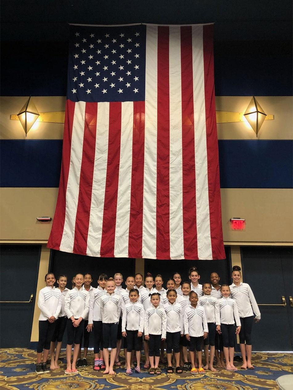 Team Posing Below the US Flag