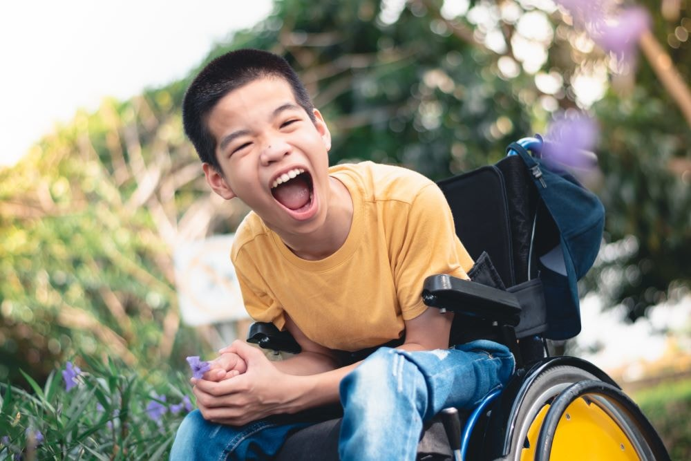 Cute disabled child on wheelchair is playing, learning, exercising, in the outdoor city park like other people. Lifestyle of wheelchair transportation.