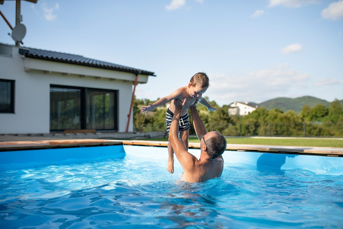 Father Holding Son up in Pool