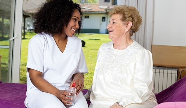 Nurse Giving Glass of Water To Elder Woman