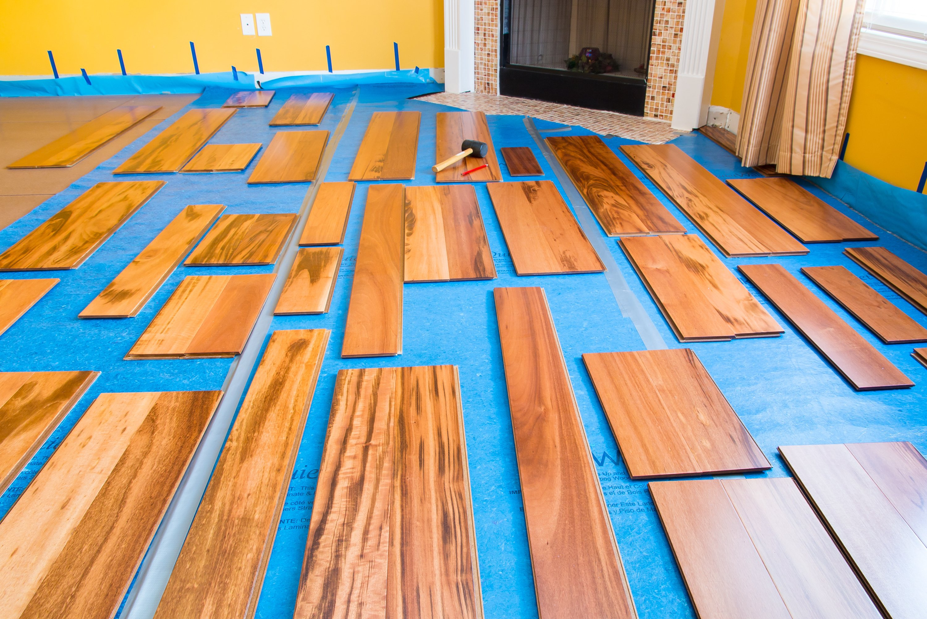 Prefinished wood planks laid out near fireplace