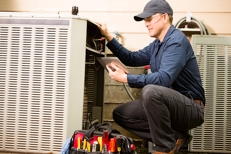 Air conditioner repairman working on home unit