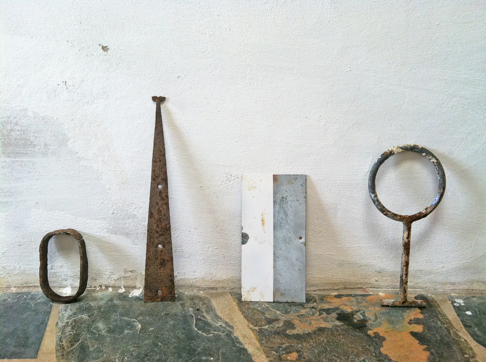 Four rustic metal objects sit on a flagstone floor and lean against a white wall.