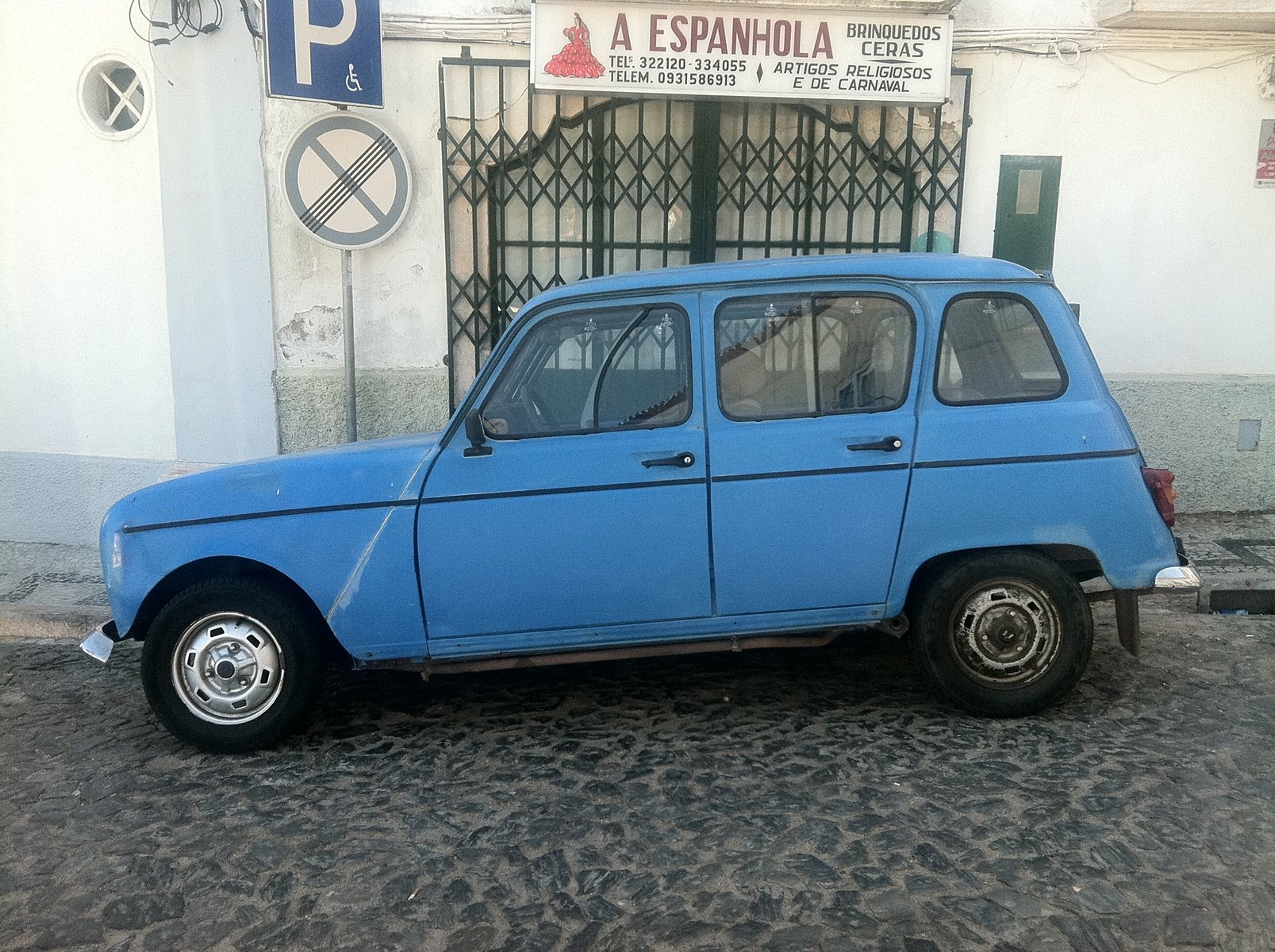 A blue car parked on a cobbled street with white walls, a metal gate and signs.