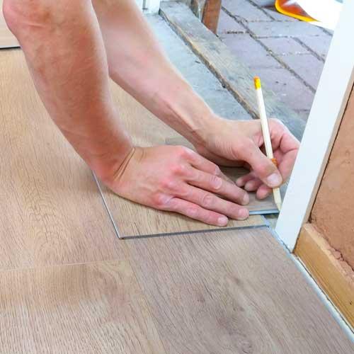 Worker Hands Installing Laminate Floor