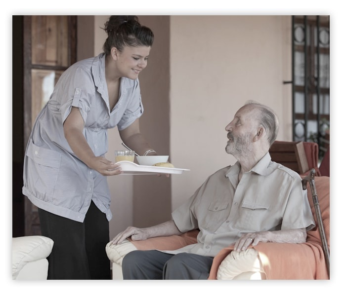 Helper in Residential Home Giving Food