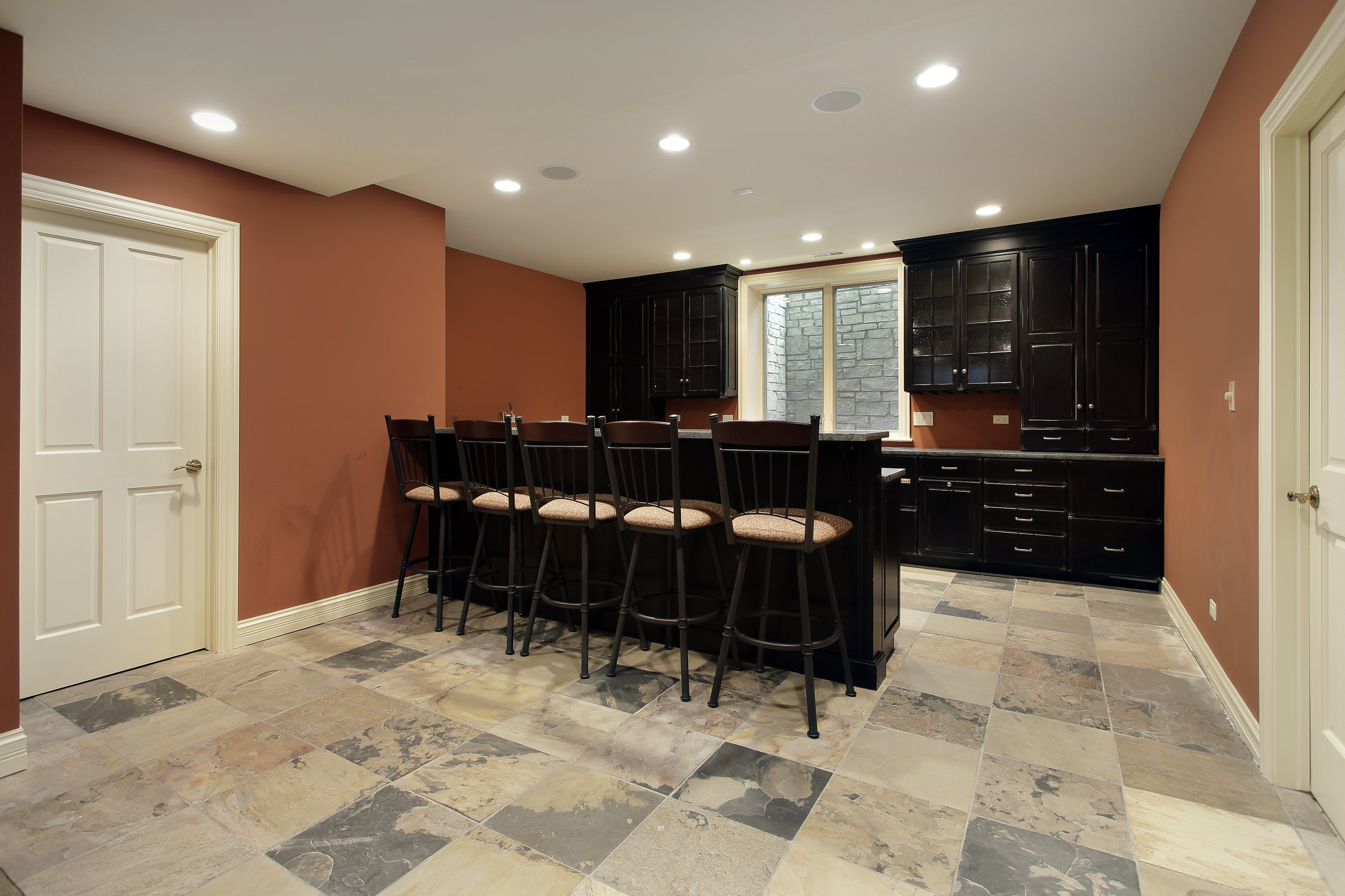 Basement Remodel with slate like ceramic tile with beautiful espresso cabinetry and bar with seating.