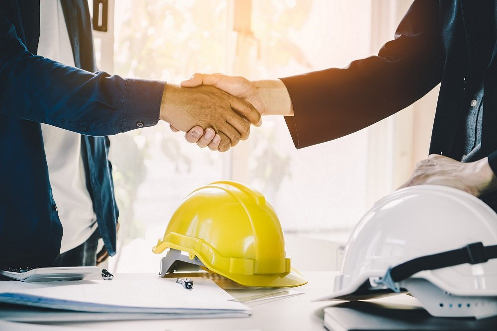 Shaking hands over hard hat