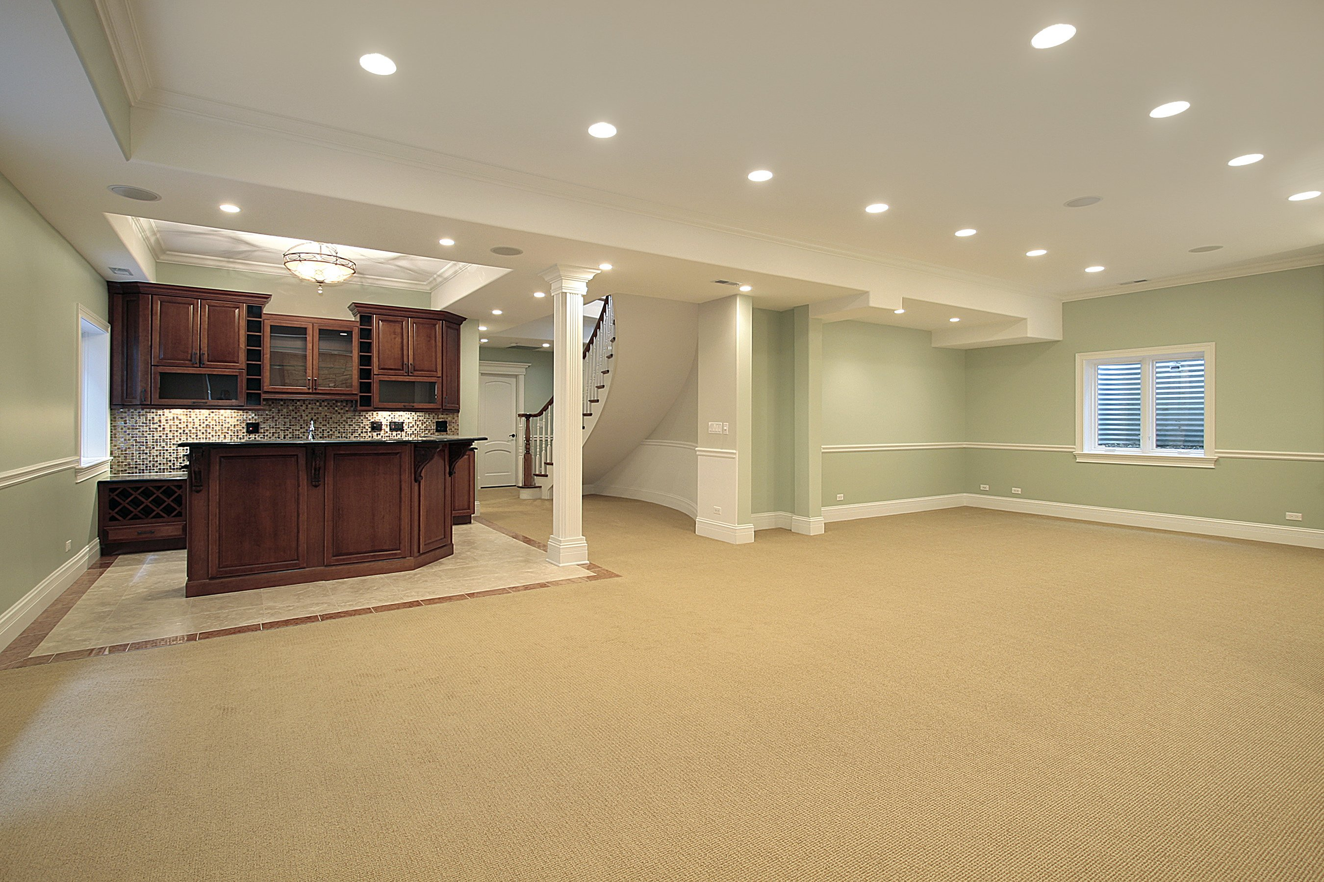Basement Remodel with luxurious bar, chair rail molding on walls.