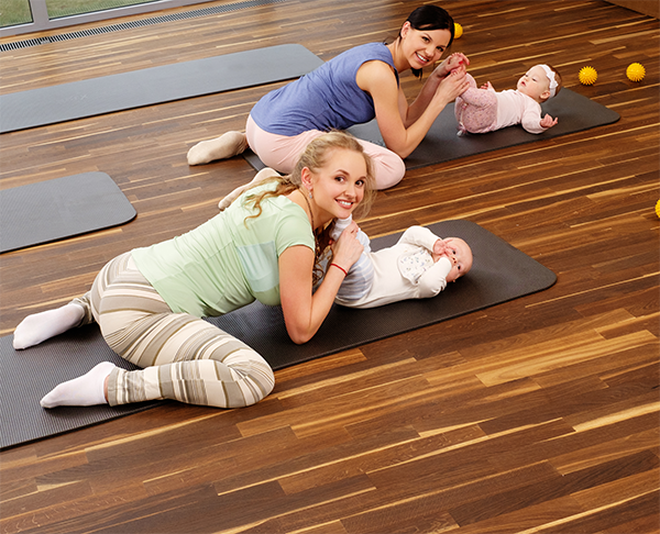 Group Of Young Mothers And Their Babies Doing Yoga Exercises