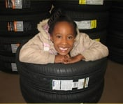 Little Girl Smiling in Tires