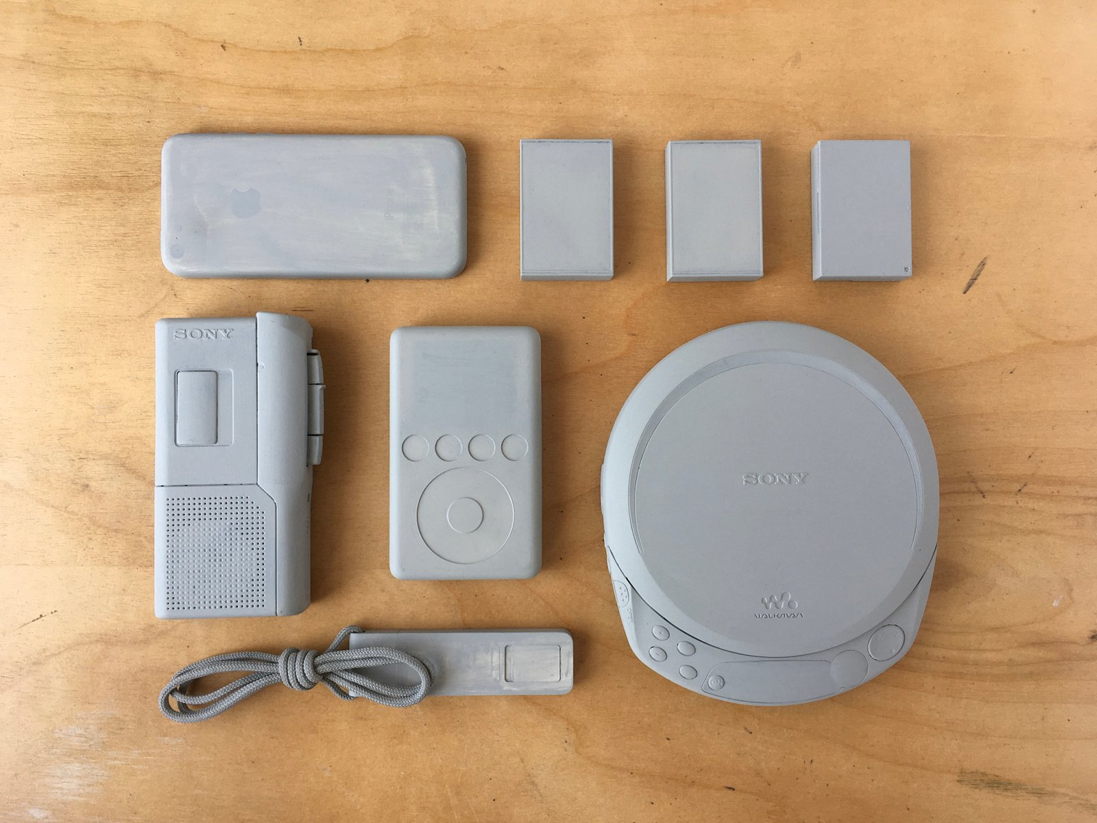 Eight Sony and Apple personal devices and micro cassette tapes painted grey.